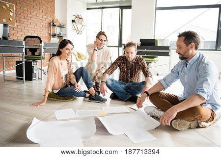 Cheerful coworkers are sitting on floor and looking at sheets of paper. They discussing certain issue