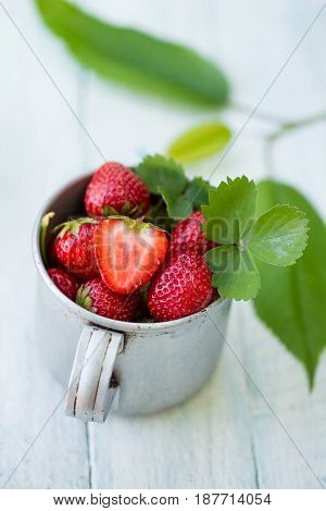 Fresh strawberries in an old metal cup