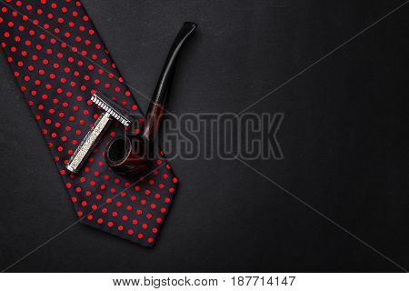 Classic Tie With Wooden Tobacco Pipe And Razor On Black Background With Space For Text, Top View. Gr