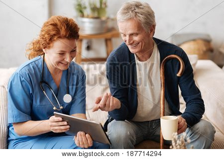 Curious gentleman. Cheerful experienced lovely therapist showing something interesting to elderly man for making him feel better while paying him a weekly visit