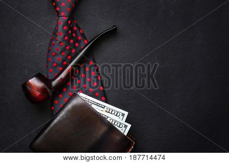 Father Day Concept Flat Lay. Bow Tie Leather Wallet With Money Wooden Tobacco Pipe On Black Backgrou