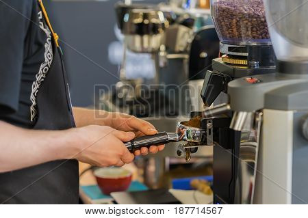 Professional grinding freshly roasted coffee in espresso machine. Barista preparing coffee in a coffee shop. Professional coffee making, service, catering concept