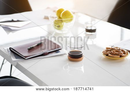 Coffee break for workers. Cups of dark non-alcoholic beverage are on table near plate with cookies and data. Nobody