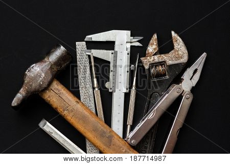 Tools For Repairing And Renovation Concept On Black Background Top View. Hammer Pliers, Screwdriver,