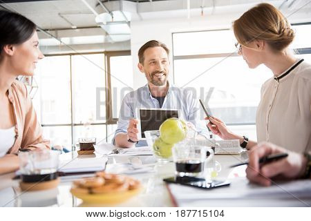 Happy manager is sitting near table and looking at colleagues with bright kind smile. He holding tablet. Woman glancing at gadget. Portrait