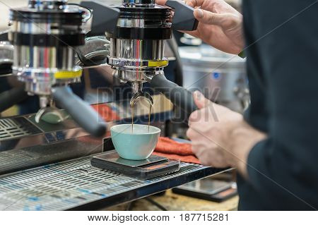 Making coffee in coffee machine. Man's hands prepares coffee, fresh espresso pours into porcelain cup. Concept of service and catering