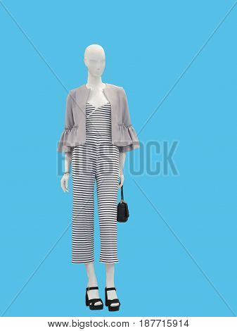 Full-length female mannequin dressed with fashionable modern clothes over blue background. No brand names or copyright objects.