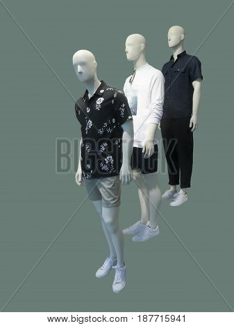 Full-length three man mannequins dressed in summer casual clothes over green background. No brand names or copyright objects.