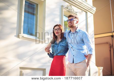 Happy funny couple standing outdoors at street of city and laughing on the bright sunny day and green summer background
