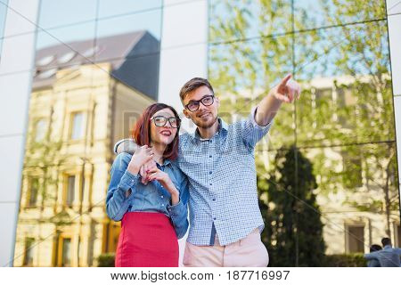 Happy funny couple standing outdoors at street of city and laughing on the bright sunny day and green summer background. The man pointing to something