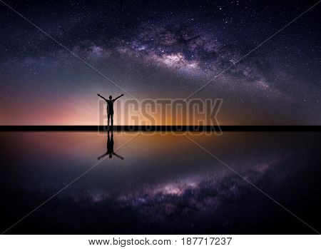 Landscape with Milky way galaxy. Night sky with stars and silhouette happy man on the mountain. Long exposure photograph.
