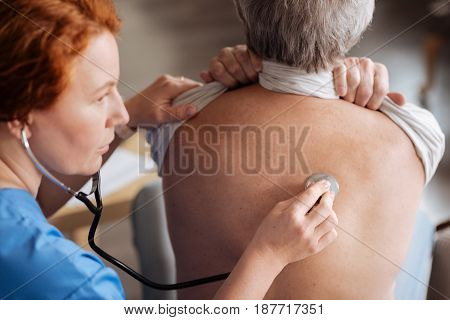 Take a deep breath. Skillful trained private doctor using professional stethoscope for hearing how elderly man breathing and diagnosing him