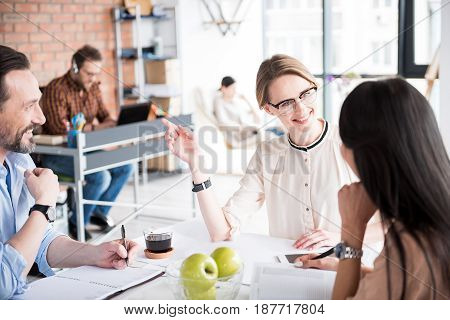 Cheerful female manager is looking at subordinates with kind smile. They discussing certain case. Portrait