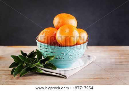Tangerine Fruit and Green Leaves on Vintage Wooden Board Background