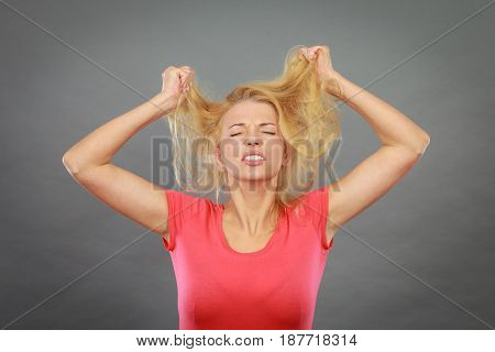 Haircare health problem concept. Frustrated depressed woman holding and pulling out her damaged blonde hair with closed eyes.