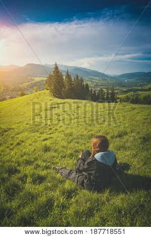 Tourist sitting on a hill in a green grass and enjoy carpathian mountain valley. Ukraine Europe. Instagram stylisation.