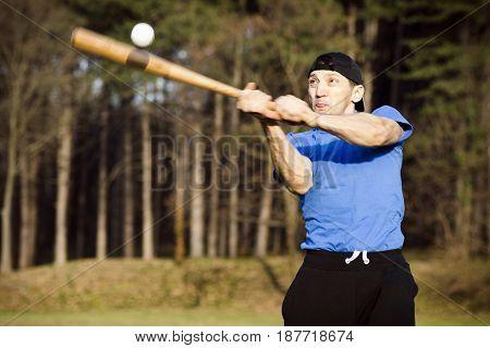 The baseball player is playing baseball outdoors.
