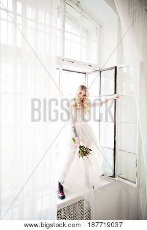 Beautiful Young Blonde Fiancee with Bridal Hairstyle Event Makeup and Flowers Opening the Window. Fashion Model Woman wearing White Dress