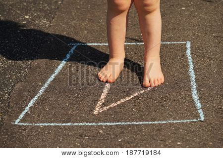 Children's legs on a asphalt road in summer
