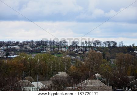 A Rural Landscape With Many Private Houses And Green Trees. Suburban Panorama On A Cloudy Afternoon.