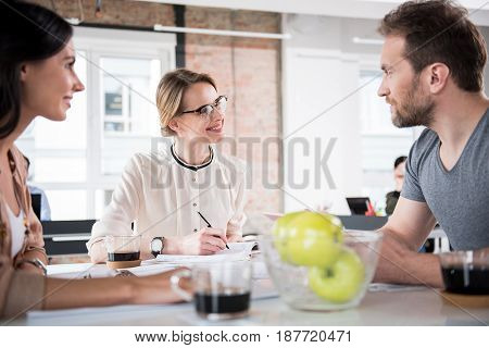 Happy director is looking at attentive subordinates with bright smile. They sitting around table and having conversation