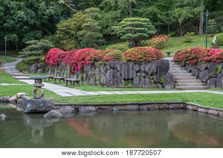 A walkway is in front of a rock wall with flowers at a Seattle garden.