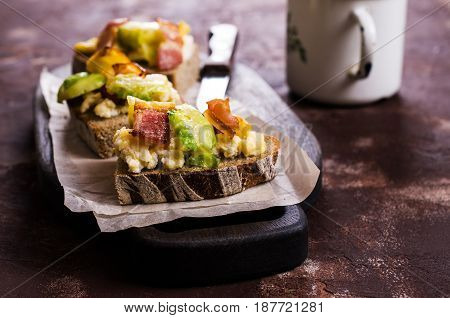 Sandwich with vegetables bacon and scrambled eggs. Selective focus.