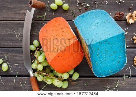 Cheese shop assortment. Gouda pesto lavender, blue, violet and red on rustic wood top view