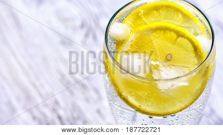 Cold mineral water with ice and lemon.