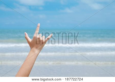 Beach love hand sign over blue sea and sky background summer travel holiday vacation concept background