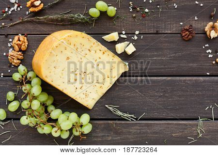 Cheese background. Gouda with herbs on rustic wood top view with copy space