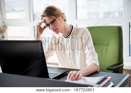 Sad female employee is looking at screen of laptop with nervous glance. She sitting near table