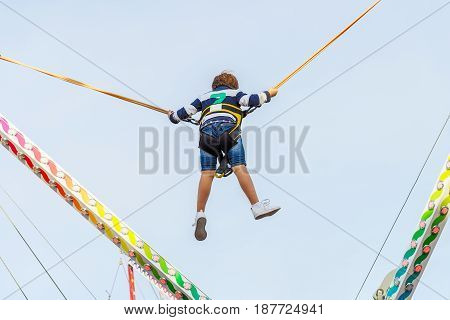 child jumping on the elastic band ride against the blue sky