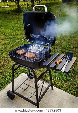 Port Charlotte, FL, USA - 04/28/2016: Garden portable BBQ cooking burgers and foil wrapped beans