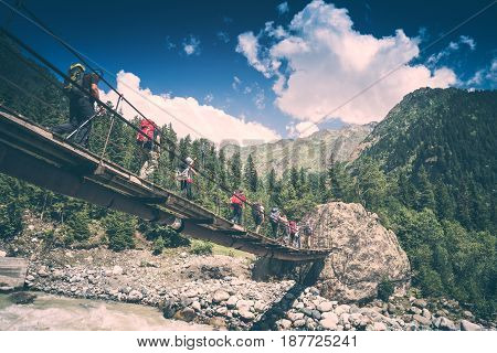 Group of hikers with backpacks go on a suspension bridge over the mountain river. Caucasian mountains Georgia Svaneti region. Instagram stylisation.