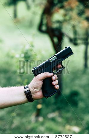 The gun is in his hand. The man is ready to shoot at the target