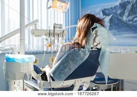 Patient sitting on dental chair, waiting for her dentist. Dental medicine, dental care, prevention, health concept.