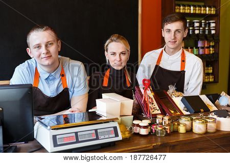 Grosery shop staff, sale clerks at counter waiting for clients. Male and female assistants