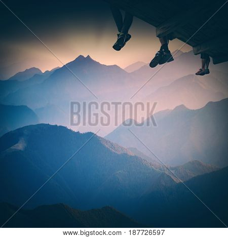 Group of hikers sit on a wooden flooring above the mountain valley and enjoy majestic sunset. Instagram stylisation.