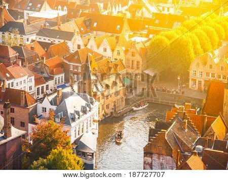 Aerial view of the dock of the Rosary and red rooftops of Bruges, aka Brugge, Belgium. On sunny autumn day with sun flare.