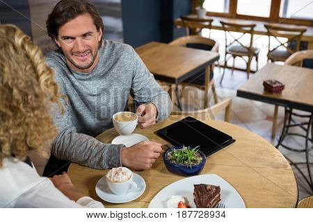 High angle view of man having coffee while talking with woman in cafe