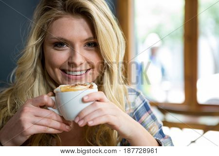 Portrait of smiling young woman having coffee in cafe
