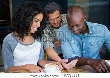 Multi ethnic male and female friends using mobile phone in coffee shop