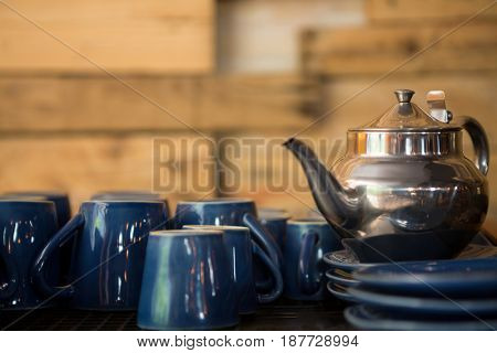 Kettle with cups and saucers on counter in coffee shop