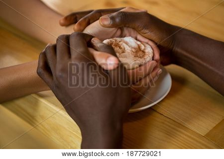 Close-up of couple holding hands and coffee cup in coffee shop
