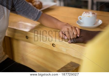 Cropped image of multi ethnic couple holding hands in coffee house