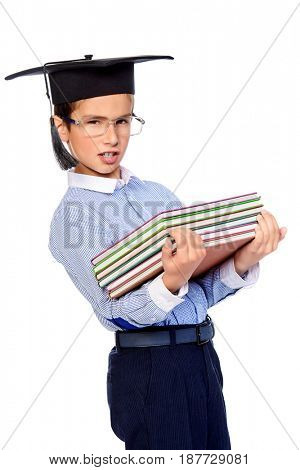 Smart school boy in academic hat and glasses standing with books. Educational concept. Isolated over white background.