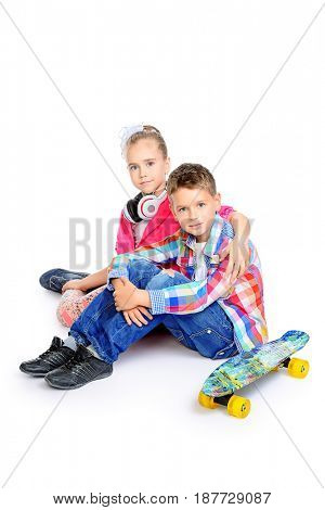 Two beautiful smiling children, a boy and a girl posing together in bright clothes. Children's fashion. Isolated over white background.