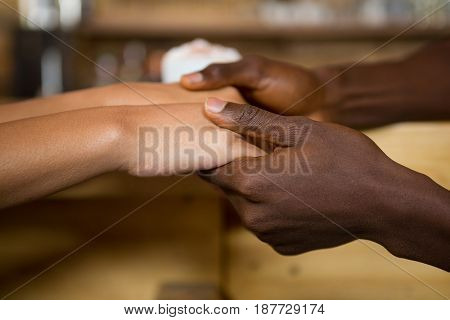 Close-up of multi ethnic couple holding hands in coffee house