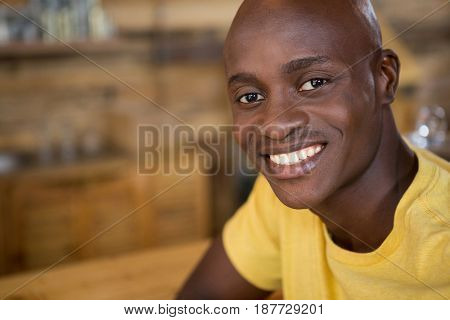Close-up portrait of young man smiling in coffee house